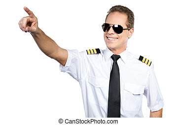 In love with sky. Confident male pilot in uniform pointing away and smiling while standing against white background