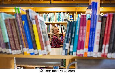 in mezzo, femmina, sorridente, scaffali, biblioteca