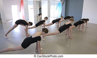 In model school beautiful and young women are stretching and holding pose