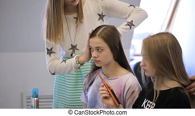 In model school woman is waiting her hair done in hairstyle.