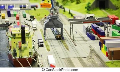 in modern toy sity train bring tank-wagon on rail to storage station in port near transport ship