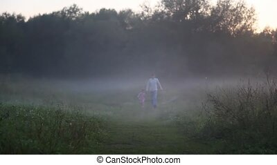 in morning in fog girl with daddy run in park on footpath...
