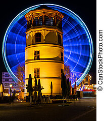 In motion - illuminated giant wheel behind the castle tower of Dusseldorf at night, Germany.