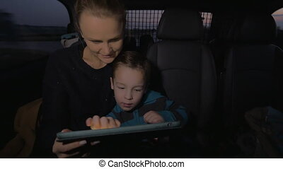 In Nea Kallikratia, Greece in car rides mother with a young son, who plays on the tablet