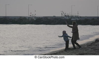 In Nea Kallikratia, Greece on sea coast a young mother with a small son throwing small rocks into water