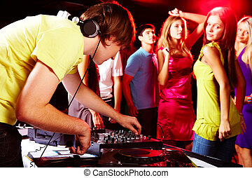In night club - Smart deejay adjusting technics with dancing...