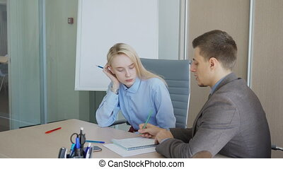 In office at desk chief gives employee an assignment on paper. Businessman explains to business woman on document strategy for business development.