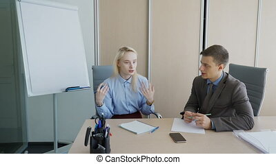 In office business man listens to woman who is gesticulating at desk.