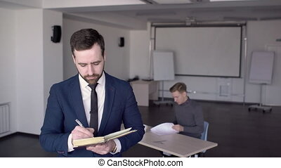 In office is a portrait of a business man who makes notes in...