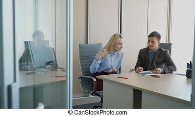 In office woman answers questions of business man at an interview.