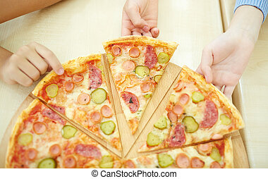 In pizzeria  - Children taking pieces of pizza