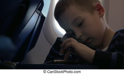 In plane sits a little boy and playing games on the mobile phone