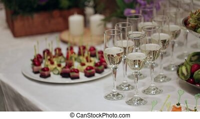 In poured a glass of champagne, the bubbles go up, a table decorated with flowers