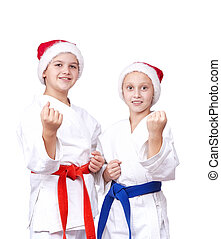 In rack of karate are children in caps of Santa Claus