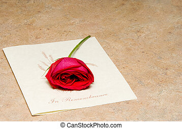 In Remembrance - A single rose on a funeral bulletin.