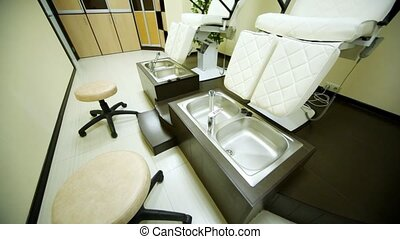 In room for pedicure in beauty salon there are special seats and cabinet