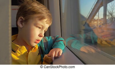 In Saint-Petersburg, Russia in train rides a little boy who looks out the window and holding a toy