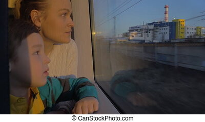 In Saint-Petersburg, Russia in train rides a young mother with a son and looking out the window