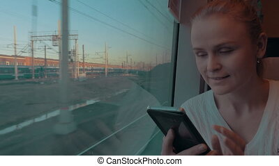 In Saint-Petersburg, Russia in train rides young girl and looking out the window, holding a cell phone