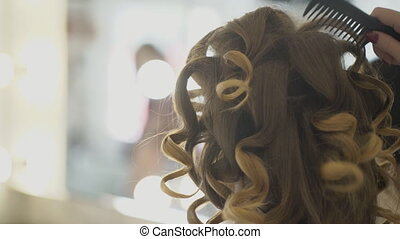 In salon hairdresser combs large curls on her long hair....