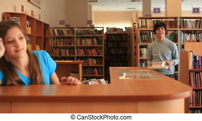 In school library - A boy returning books in library and a...