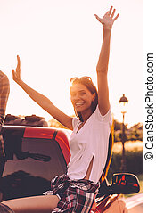In search of adventures. Beautiful young woman keeping arms raised and smiling while enjoying road trip in pick-up truck