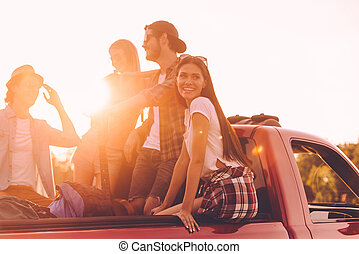 In search of great adventures. Group of young cheerful people enjoying their road trip while sitting in pick-up truck together