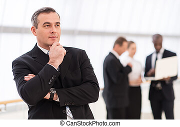 In search of the new ideas.  Thoughtful mature man in formalwear holding hand on chin and looking away while his colleagues standing on background