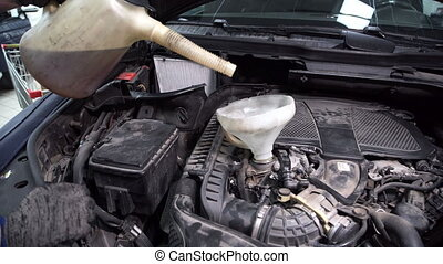 In service station mechanic through a funnel pour oil in a car engine.