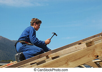 in she goes - builder driving home a nail while finishing...
