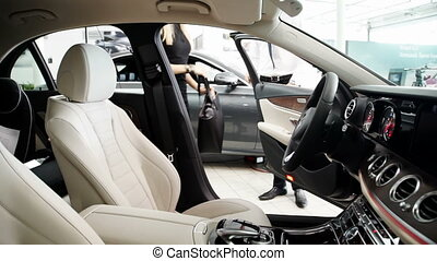 In showroom young woman to sit in the new car and explore the salon.