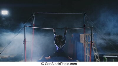 In slow motion in the smoke girl acrobat on the crossbar...