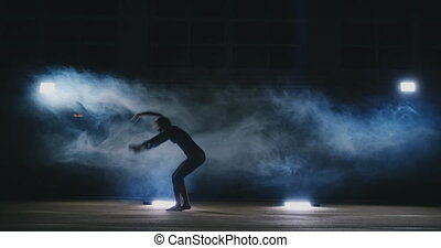 In slow motion in the smoke girl acrobat performs several...