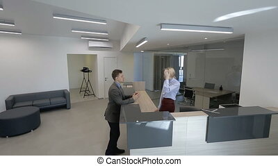 In spacious hall at reception of office man and a woman...