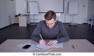 In spacious office specialist uses a pencil to draw a paper...