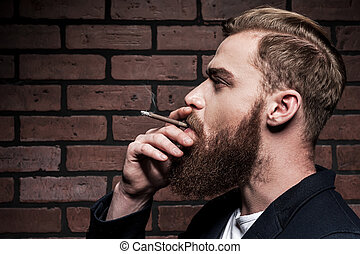 In style. Side view of handsome young bearded man smoking a cigarette while standing against brick wall