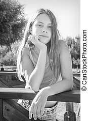 In summer, a beautiful girl stands on the bridge. Black and white photo.