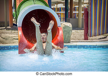 In summer, a bright sunny day at the water park, the boy slides downhill.