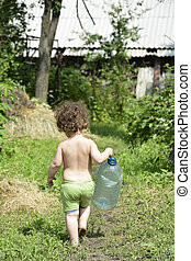 In summer, a small rural curly girl holding a large plastic bottle.