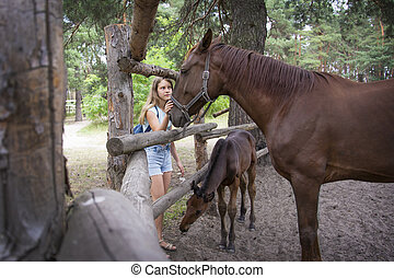 In summer, at the stable, a girl stands next to a horse with a foal.