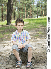 In summer, in a pine forest on a tree stump sits sad boy.