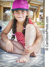 In summer, on a bright sunny day, a little girl in a swimsuit and cap sits on the beach.