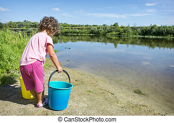 In summer, on a hot, sunny day, a small, curly girl takes water in buckets from a river.