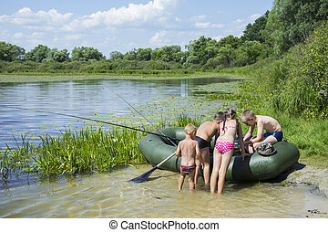 In summer, on the bank of the river, children gather for fishing on an inflatable boat.