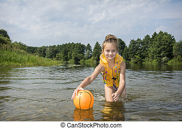 In summer, on the river, a girl in a vest plays with a ball.