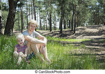In summer, the pine forest sitting on the grass blond man with a daughter.