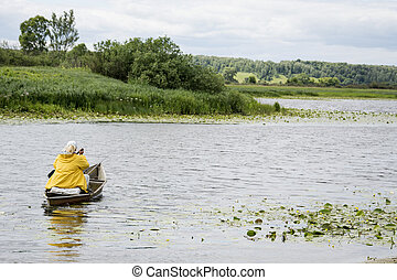 In summer, the woman fisherwoman boat floats on the river with a fishing rod.