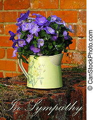 In Sympathy card with purple Campanulas in a metal jug, sitting on a brick wall