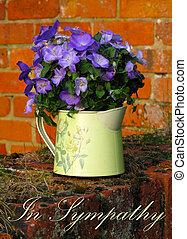 In Sympathy card with purple Campanulas in a metal jug, sitting on a brick wall