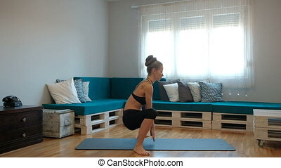 In the apartment, a woman performs squats with her hands down.